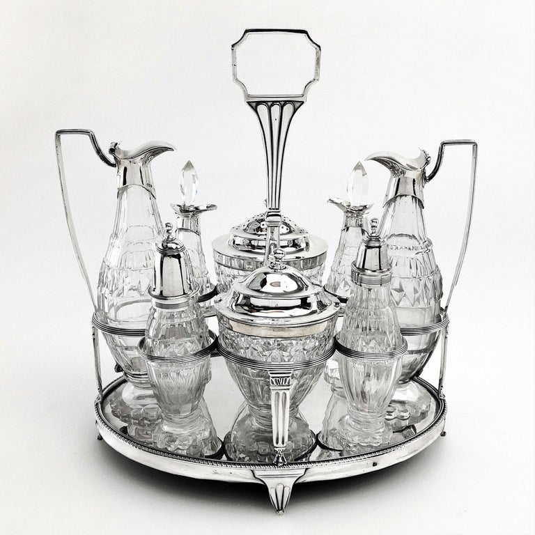 A magnificent Georgian solid Silver and cut Glass Cruet Set. This set is of substantial size and consists of a solid silver stand and 8 condiment containers. These include a mustard pot, oil & vinegar pourers, a Caster and four other containers