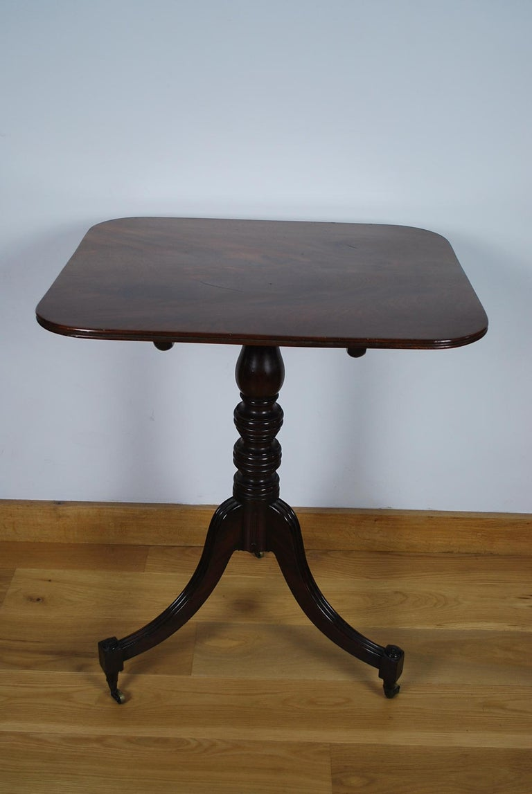 This is a very fine quality Georgian antique mahogany tripod table with rectangular top. It has out swept legs and turned feet standing on brass castors.