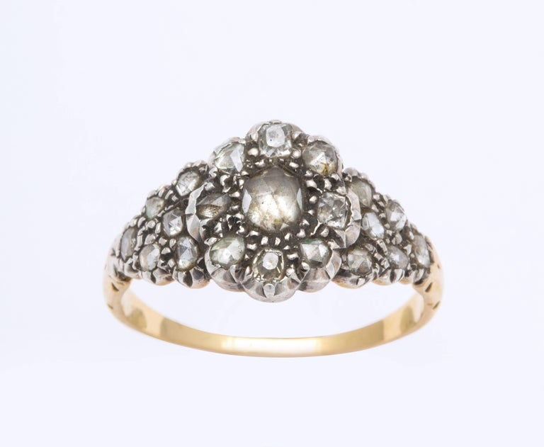 A feminine, delicate ring encrusted with .50 cts of antique cut diamonds, is set in the form of a floral cluster with diamonds spilling on to the shoulders of the shank. All but the center diamond are foiled. The ring, with the appearance of an