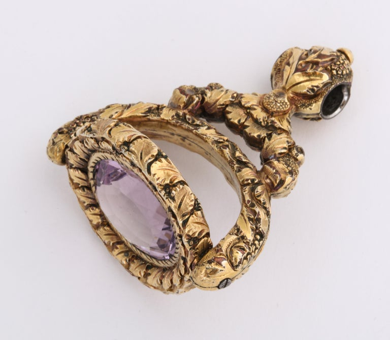 A sculptural Georgian Fob abundant with puffy engraved details of grapes and leaves that cover every surface with the exception of the huge 13 Ct amethyst at the center. The amethyst is a medium in tone chosen so as not to overpower the entire