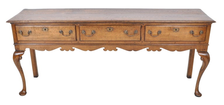 Antique Georgian oak dresser base, circa 1800. The dresser having an overhanging molded top, below three drawers with the original brass handles and escutcheons. The dresser standing on cabriole legs joined by a shaped skirt and terminating to pad