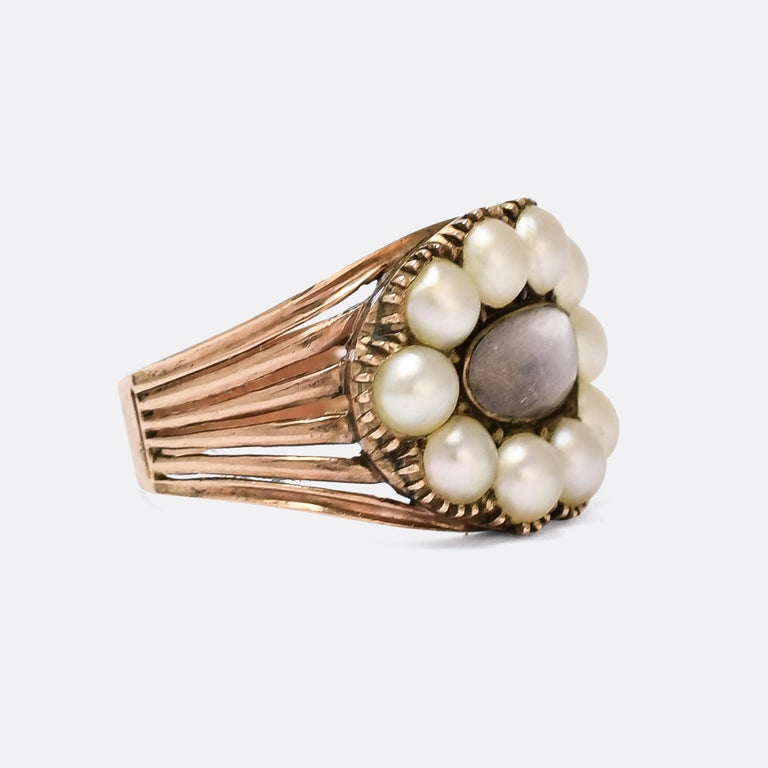 A gorgeous Georgian memorial ring dating from the early 19th Century, circa 1820. It features a finely woven locket of hair behind an oval glass compartment, within a border of natural pearls in crimped settings. The shoulders split into six