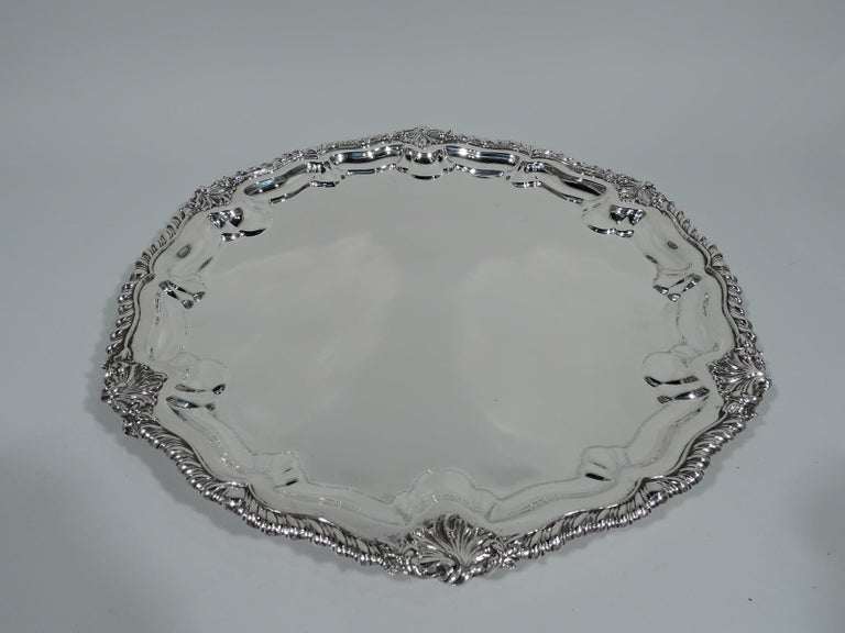 Georgian Revival sterling silver salver. Made by Howard & Co. in New York in 1905. Round with gently scrolled and gadrooned rim interspersed with scallop shells. Rests on three scallop shells supports. A beautiful piece in the traditional style.