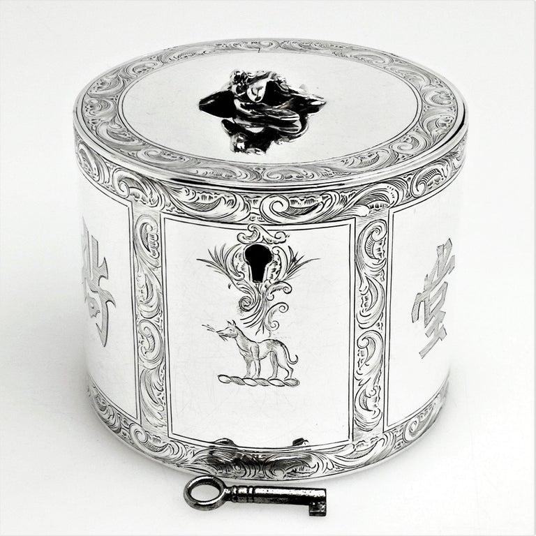 A beautiful Antique George III solid silver tea caddy. This caddy has a circular straight sided can shaped form and is decorated with beautiful and detailed engravings. These engravings form ornate scroll borders created panels on the sides. One of