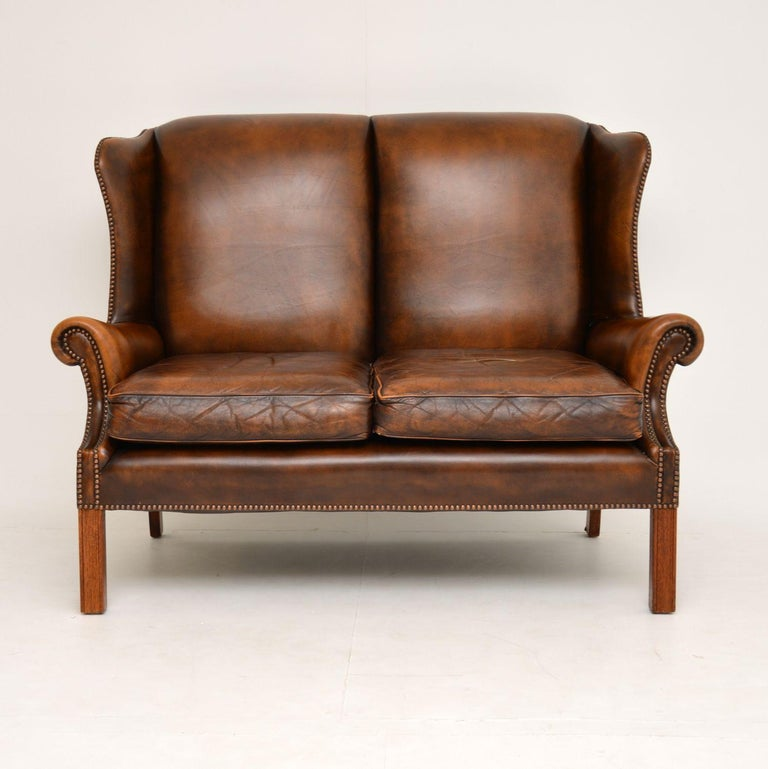 Very comfortable antique Georgian style two-eat wing back sofa in good original condition and dating from circa 1960s period.