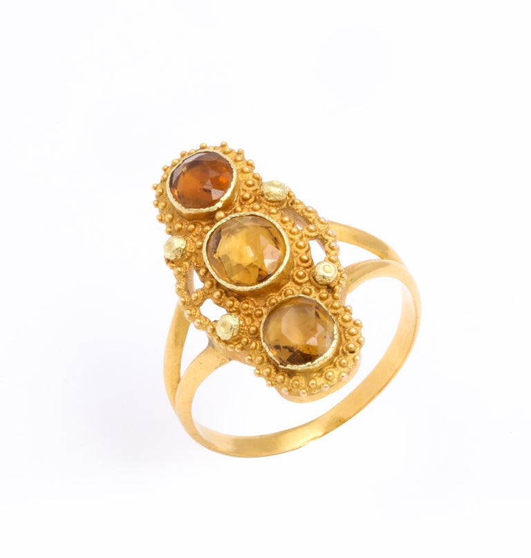 Three oval citrine gems are vertically set in 18 Kt Gold in this Georgian ring. The citrine look as if drops of honey spiked into place on this three stone setting. Superb gold work stands out in the smallest spirals of cannetille work and the