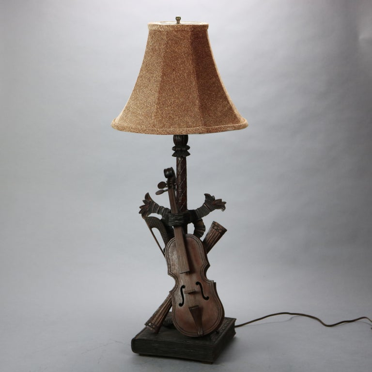 Antique German Black Forest table lamp offers carved sculptural base with music instrument grouping to include violin, bow and book, wired for US electrical use, c1880  Measures - overall 34.25''h x 14''w x 14''d; shade 14'' diameter; base 9'' x