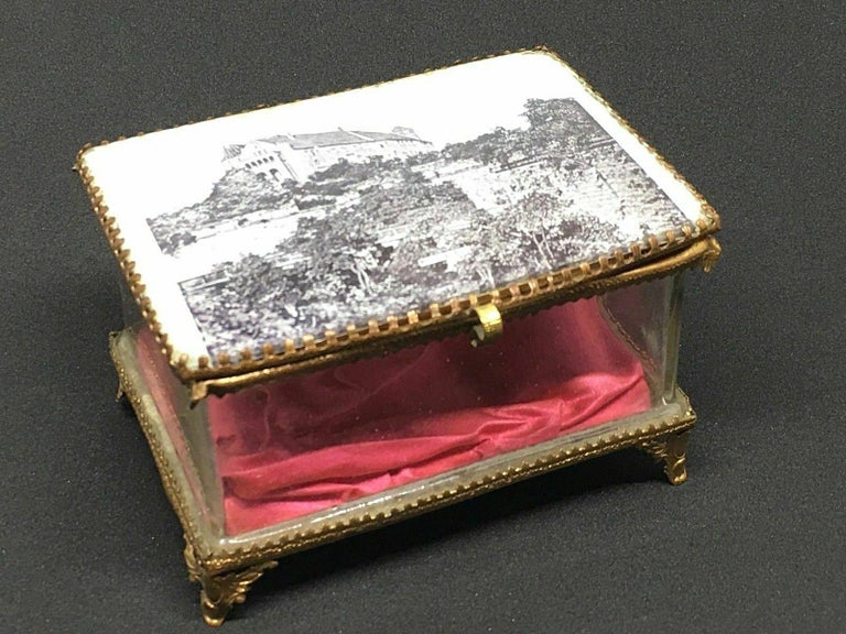 A gorgeous glass trinket box with some ormolu adornments. The hinged top featuring a City view of the Nuremberg Castle. No restoration has been carried out on this charming little trinket box, which remains in very stabile and functioning condition,