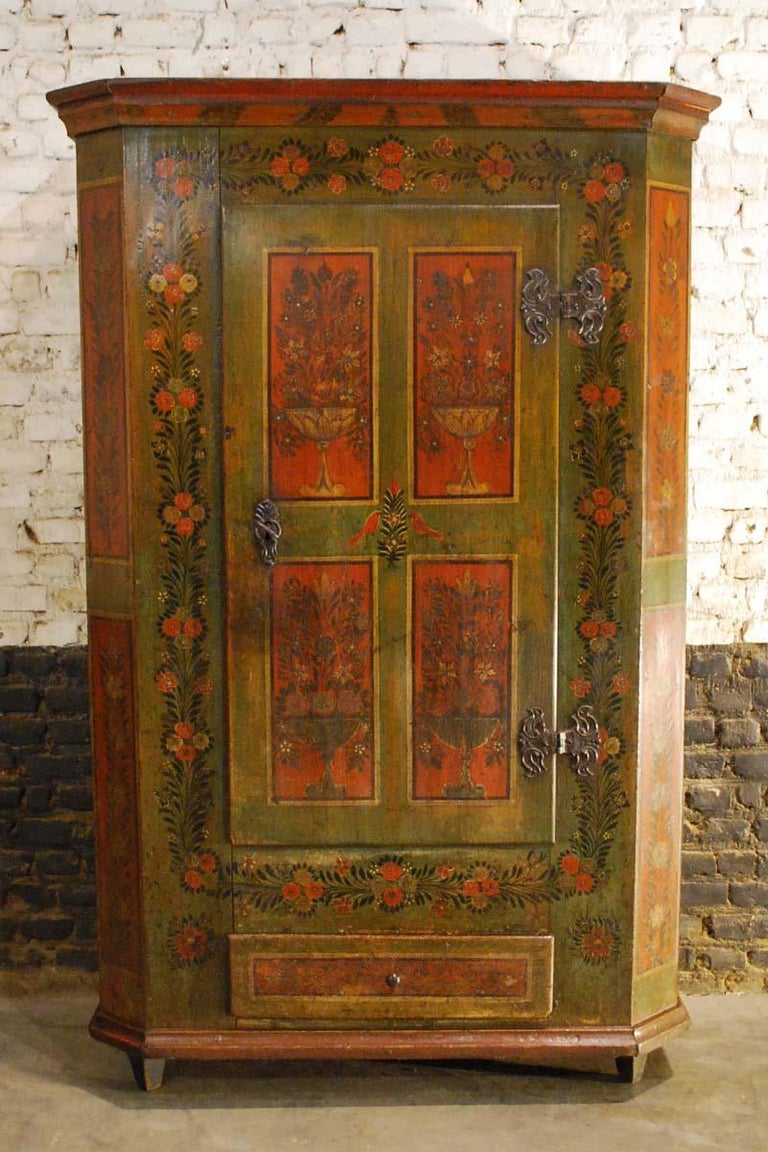 A beautiful single door cabinet from rural southern Germany, dating circa 1820. This cabinet is made in solid pine and is painted in a very elegant and refined manner. It has a green base color with red paneling and is decorated with garlands and