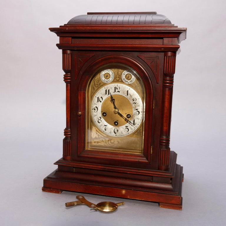 An antique German Junghan bracket clock offers mahogany case with incised domed top surmounting paneled case having arched face with flanking balustrade supports, raised on stepped base, with key, circa 1910.