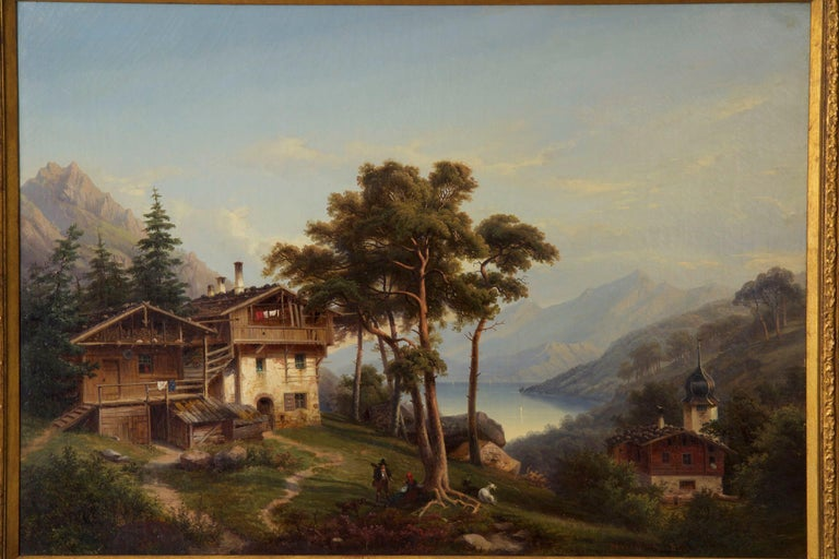An exceptional genre scene of a German landscape under a nearly cloudless sky, a large wood and stone chalet is tucked into a grove of pine trees overlooking the blue lake below. Mountains loom in the distance while a hiker and his dog chat with a