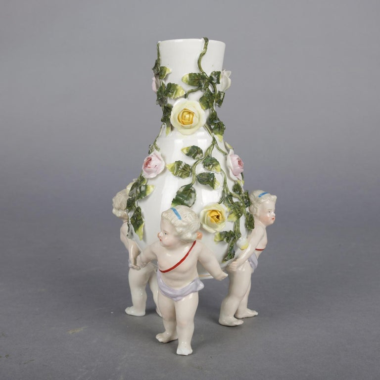 An antique figural German Meissen Porcelain bud vase features vessel with bulbous form and flared neck having all over applied and hand painted floral roses with leaf and vine, raised on three cherub form legs, crossed sword mark on base, circa
