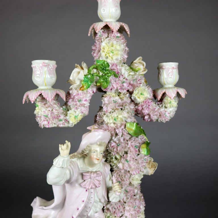 A figural German Meisen School garniture set includes pair of three light candelabra and central footed bowl in hand painted porcelain with all-over applied floral and foliate decoration, the candelabra each with male and female courting couple