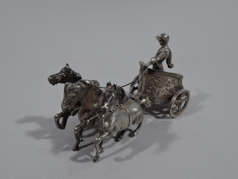 Antique German 800 silver miniature Roman chariot, ca 1900. A u-form vehicle with tunic-clad man casually holding the reins of three galloping horses. The wheels really rotate. Evocative of male vigor and pounding horse flesh. Marked.