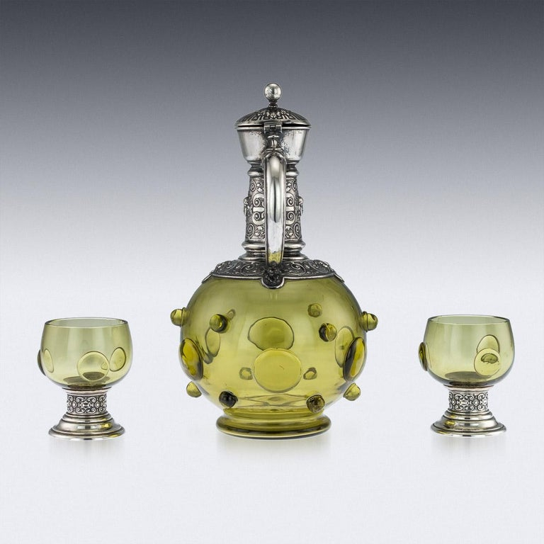 Antique late-19th century German solid silver and green glass decorative wine claret jug and pair of goblets, bulbous green glass body applied with unusual ball decoration, the silver mount is chased with Cellini inspired classical motifs, c-shaped