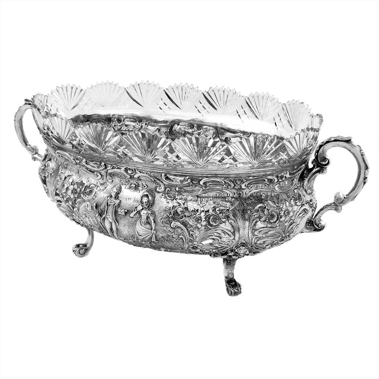 A magnificent antique German solid Silver Bowl with a ornate chased design on the body and two scroll handles. The chased designs show detailed classical scenes surrounded by elaborate floral and scroll designs. The Bowl has a fitted clear glass