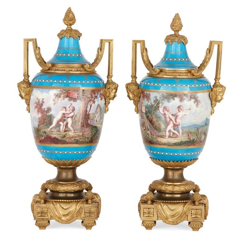With its exquisite paintings of putti playing sports in Arcadian landscapes, this 'bleu celeste' garniture demonstrates the exceptional beauty and high-quality craftsmanship of Sevres factory porcelain. In addition to this, the porcelain vases are