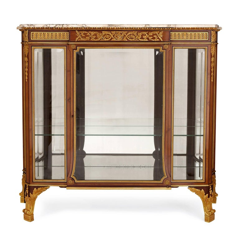 This large and grand vitrine cabinet is executed with precision and skill, and would make a well-appointed addition to any refined, luxury interior. 