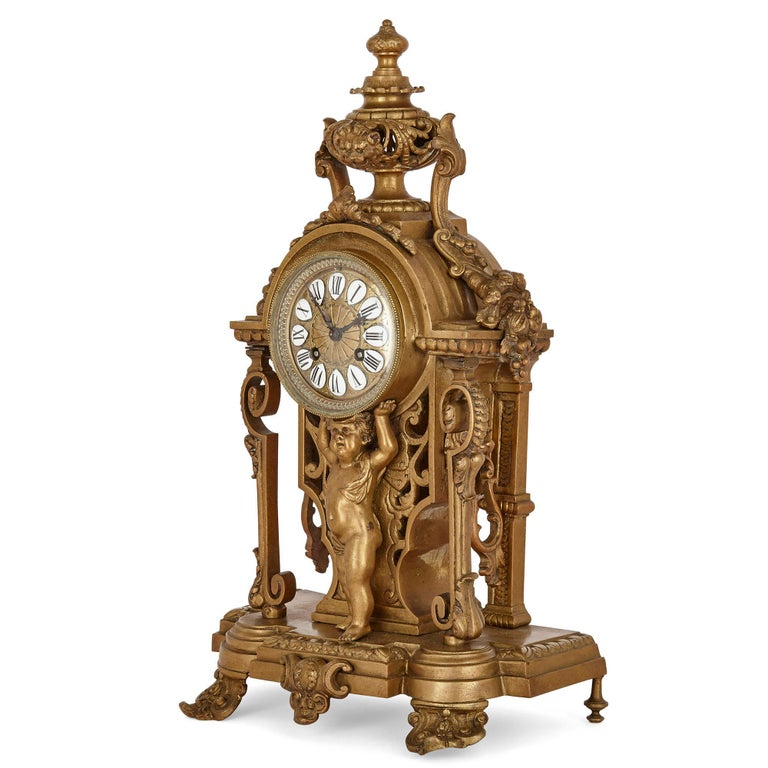 This clock set contains a mantel clock and a pair of candelabra. Unusually, the clock and candelabra are constructed entirely of gilt bronze. The bronze dial of the mantel clock is inscribed with Roman numeral hours on separate enamel cartouches.