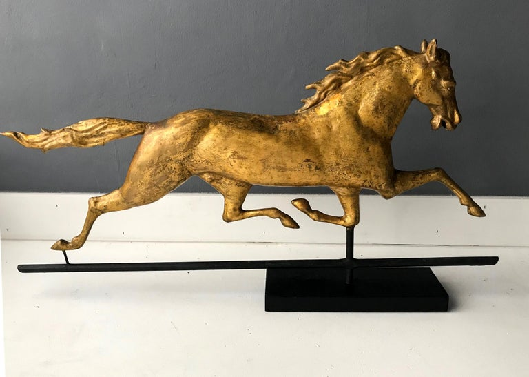 A spectacular full body running horse weather vane attributed to J.W. Fiske, on the original mount and displayed on a simple black wood base. The well sculpted horse is in a prancing stance with a lively rendering. It was removed from the Carriage