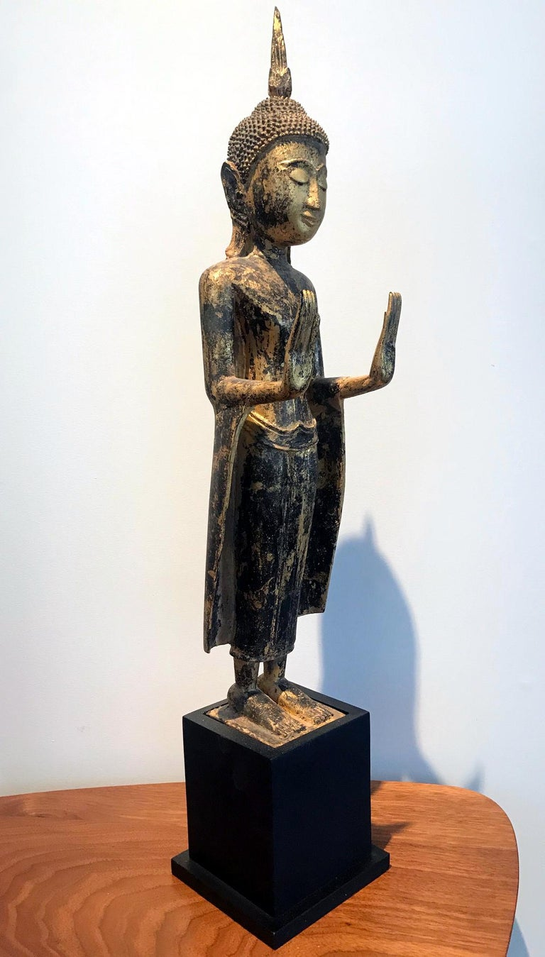 A delicately carved wood Buddha in an upright standing posture with a double Abhaya mudra. The statue displays a gilt surface with beautiful patina and some minor wear. The face was rendered with a serene expression with downcast eyes and a faint