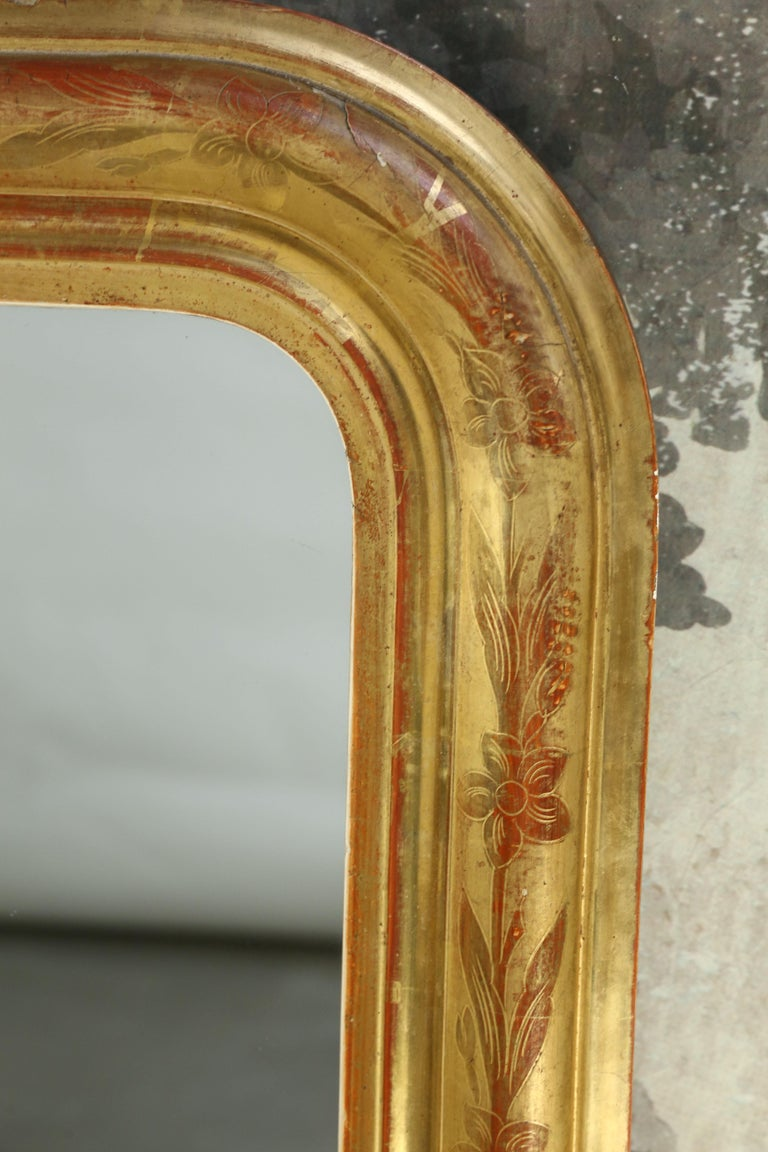 Beautiful French Louis Philippe mirror with intricate incised floral motifs. The glass mirror was probably added at a later date. Red and yellow bole has been used on this wonderful Louis Philippe giltwood mirror from the 19th century.