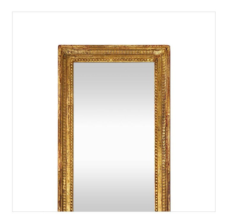 Large antique giltwood mirror, Louis XVI style, French mirror circa 1900. Antique giltwood frame decorated with fluting and pearls around the edge of the glass mirror. Re-gilding to the patinated leaf. Antique wood back. Antique frame width: 4 cm.