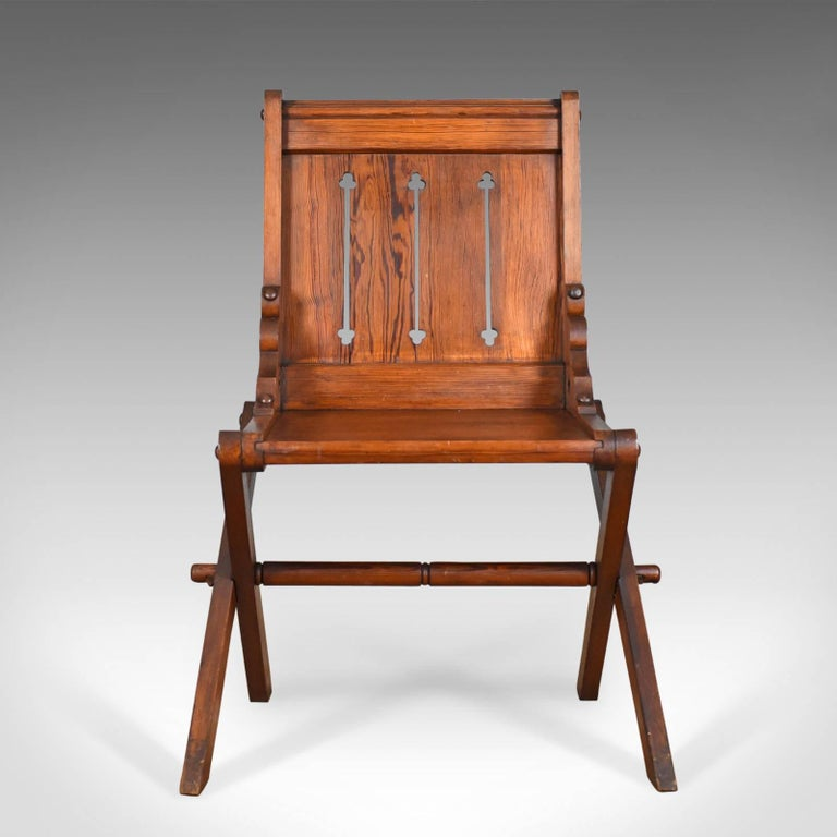 This is an antique Glastonbury chair, English Tudor Revival carved hall seat dating to the late 19th century, circa 1880.  An unusual, arm-less Glastonbury chair in pitch pine Exhibiting ecclesiastical and gothic overtones Classic tusked joints
