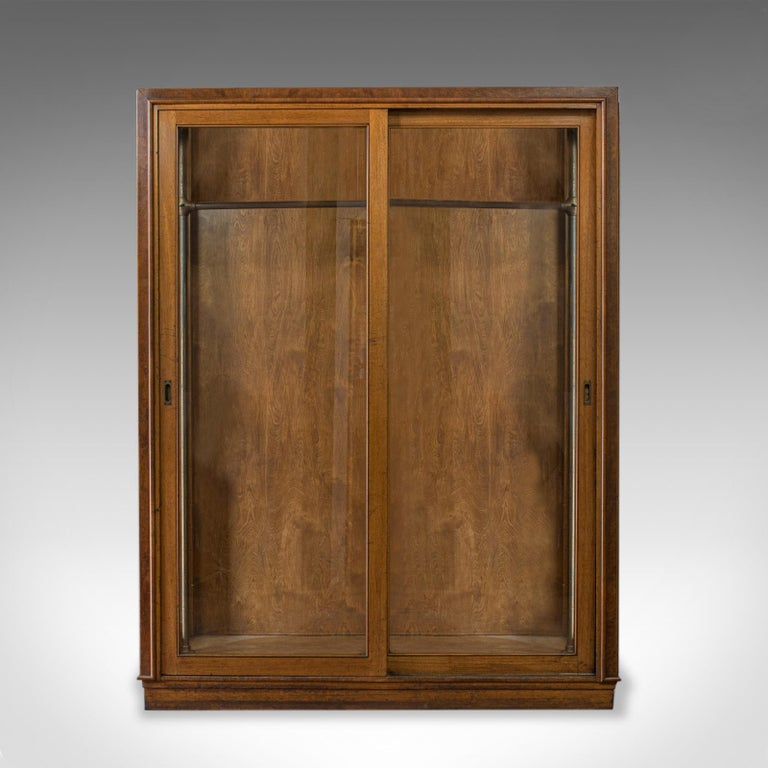 This is a substantial antique glazed wardrobe cabinet. An English, oak retail, display shop fitting cabinet by aircraft and store planning specialists George Parnall and Co, and dating to the late 19th century, circa 1900.  Select oak and burr