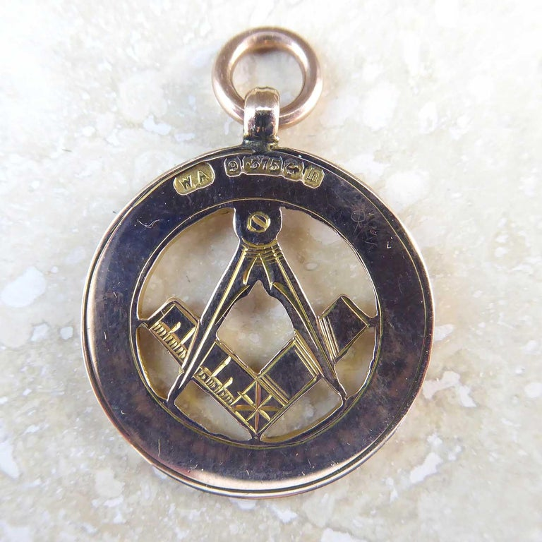 An antique gold watch chain fob dating from 1911.  The centre of the fob depicts the Freemason signs of the square and compass set within an outer border 1/8th of an inch wide and handsomly engraved with an acanthus leaf design.  The reverse of the