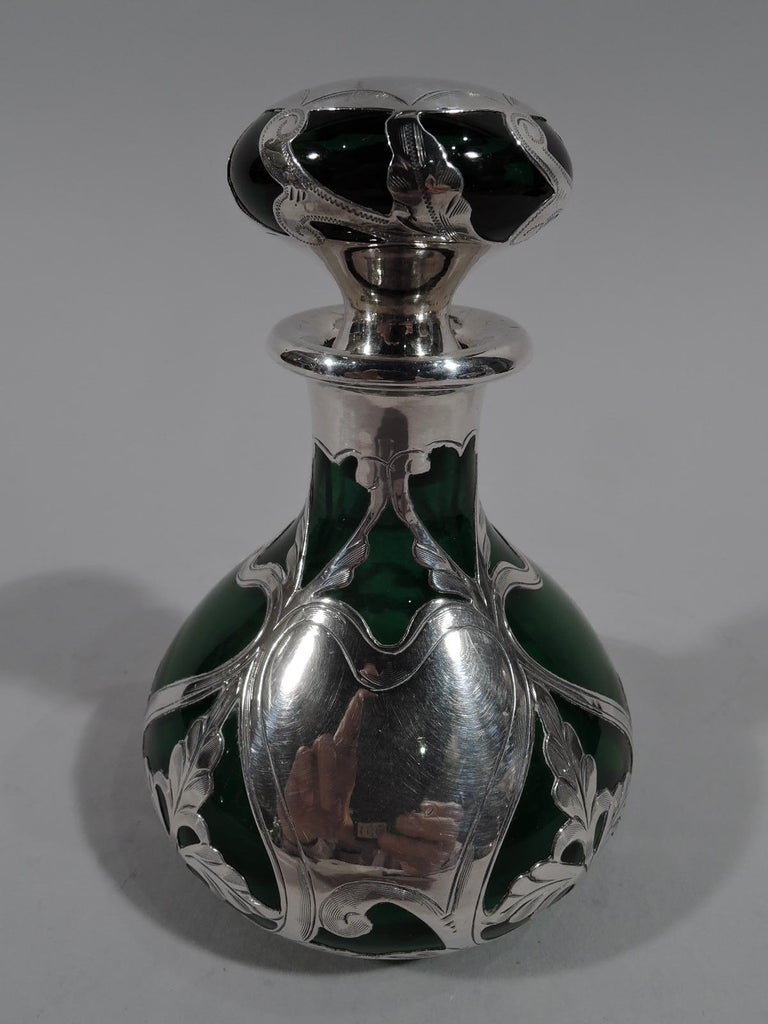 Turn-of-the-century Art Nouveau glass perfume with engraved silver overlay. Made by Gorham in Providence. Ovoid with short neck and flat rim in silver collar. Flattened ball stopper. Overlay in form of open whiplash tendril frames of which some