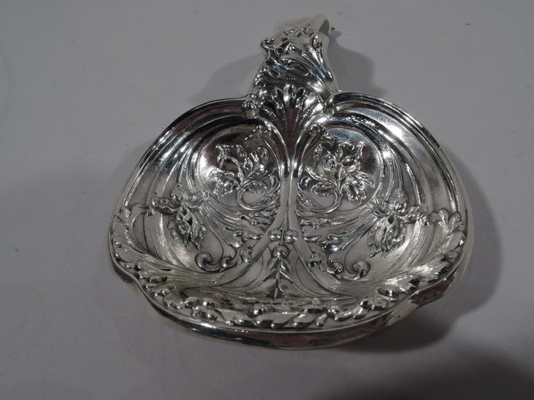 Turn-of-the-century Art Nouveau sterling silver bonbon scoop. Made by Gorham in Providence. Round shaped bowl with arched handle. Dynamic ornament with swooshing and colliding leafy scrolls. Fully marked and numbered A4224. Weight: 4.5 troy ounces.