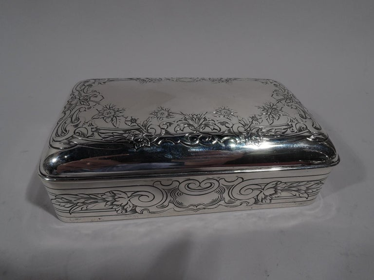 Edwardian Classical sterling silver jewelry box. Made by Gorham in Providence in 1913. Rectangular with straight sides and curved corners. Cover hinged and curved with molded rim. Box has wrapround linear bands terminating at front in volute