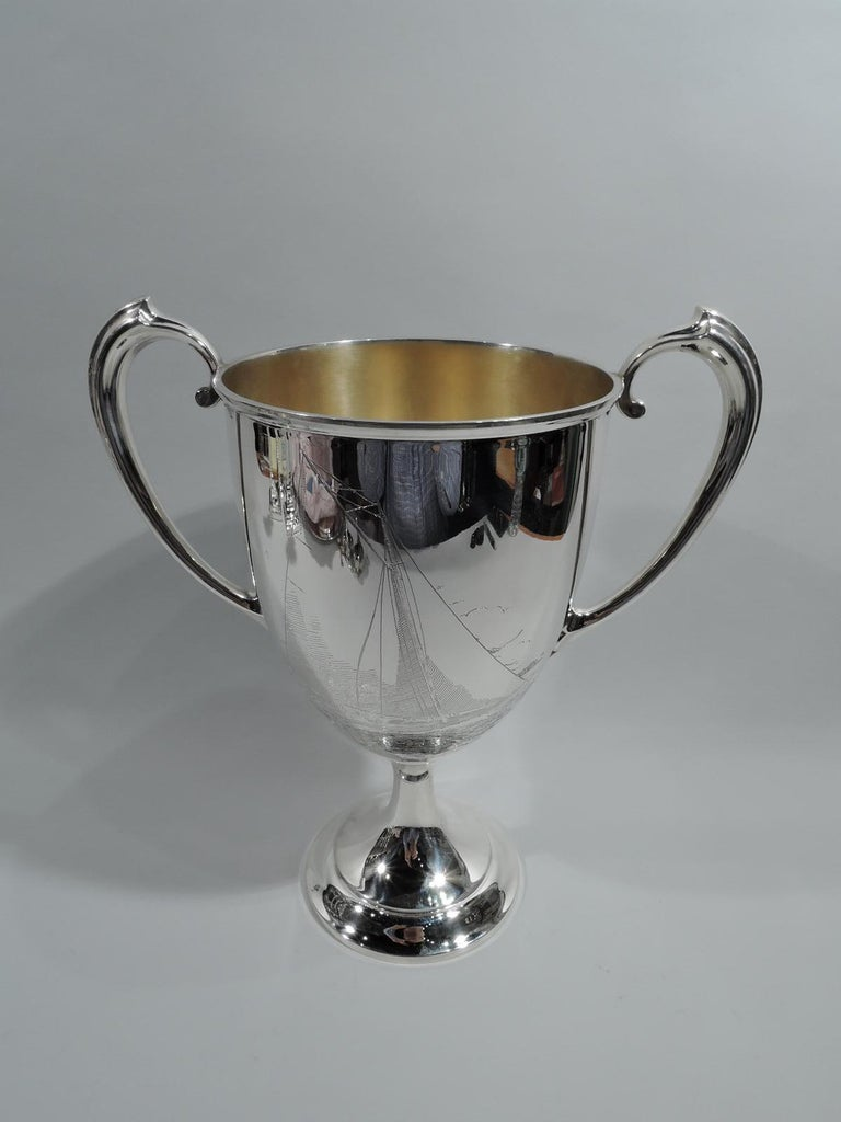 """Edwardian Neoclassical sterling silver trophy cup. Made by Gorham in Providence. Oval bowl with high-looping handles and raised foot. Engraved presentation on front: """"Inter-Lake Yachting Association / Class Q. Trophy / Presented by / Commodore Emil"""