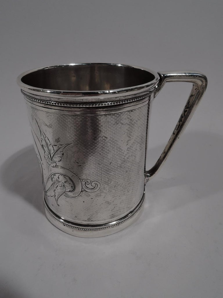 Modern Classical coin silver baby cup. Made by Gorham in Providence, circa 1865. Straight sides with skirted foot and bracket handle. Scrolled and leafy frame (vacant) on engine-turned wavy ground. Beading. Bold and sophisticated. Fully marked and