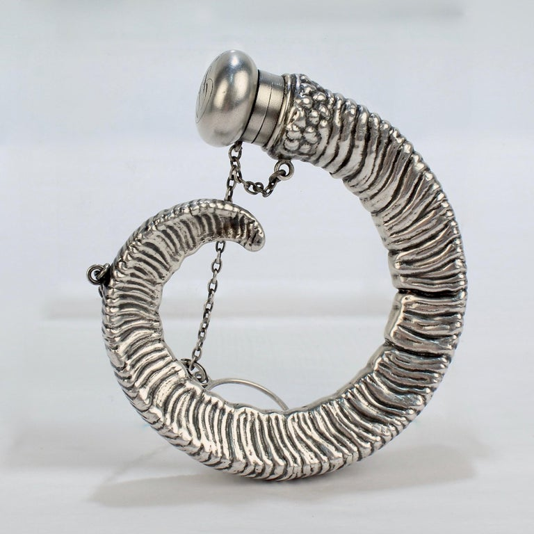 An American figural sterling silver flask in the form of a rams's horn.  The chatelaine flask was likely initially intended for perfume (and was also perhaps employed for an occasional whiskey or other tipple).   Marked to the top with the Gorham