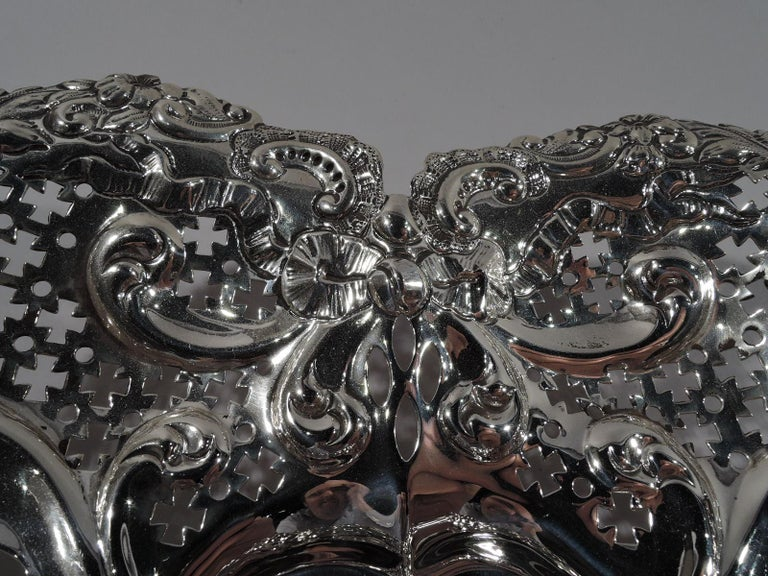 Super romantic Victorian sterling silver bowl. Made by Gorham in Providence in 1895. Solid heart-shaped well; curved and tapering sides with chased scrolls and ribbon bows and pierced geometric ornament. Irregular rim with scrolls, leaves, and
