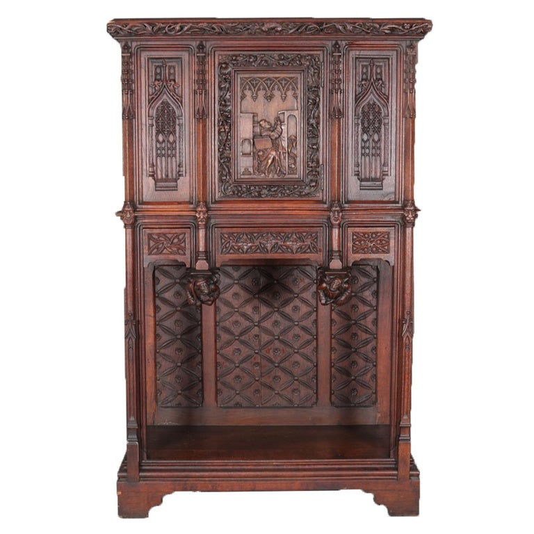An antique Gothic Revival oak cabinet features upper with central door having heavily carved pictorial scene depicting monk priest in study, flanked by panels with cathedral arch design surmounting three drawers having foliate design with figural