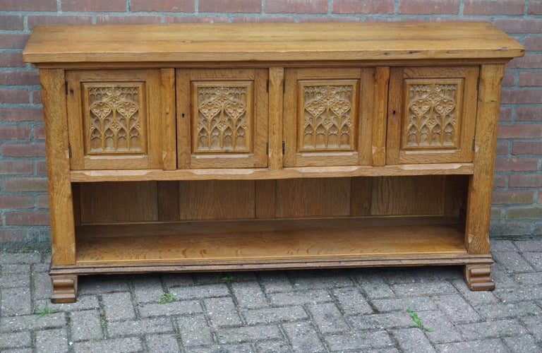 Beautiful and practical, half open design credenza.  This antique Gothic Revival cabinet can be placed tight on your wall and thanks to its wide and undeep design this medieval style beauty can be placed almost anywhere without taking up too much