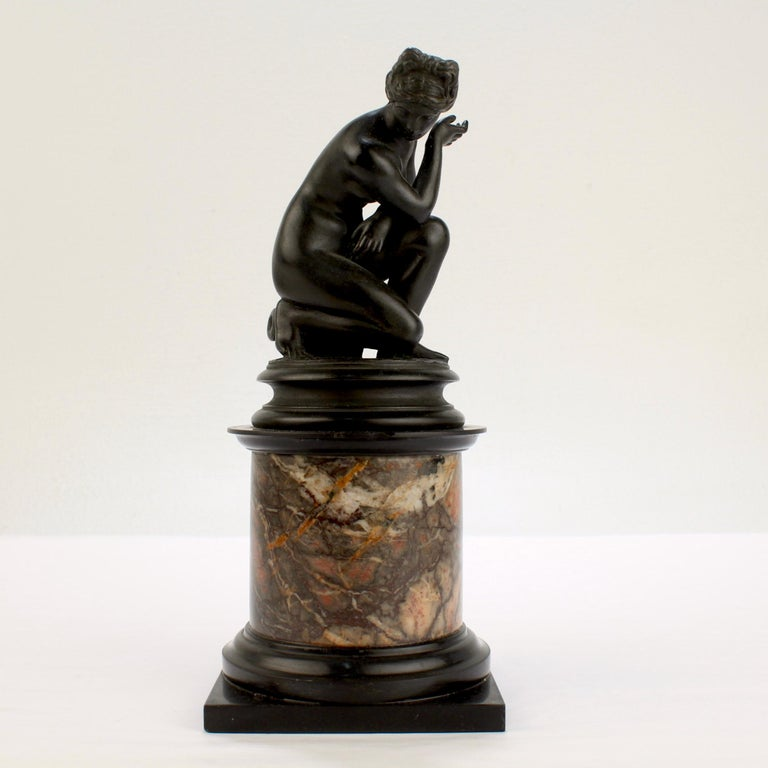 A very fine Grand Tour bronze sculpture.  Modeled after the 'Crouching Venus' by Giambologna.  Depicting Venus surprised at her bath with an overturned urn at her feet. Mounted on a slate and variegated marble plinth.   Simply a wonderful