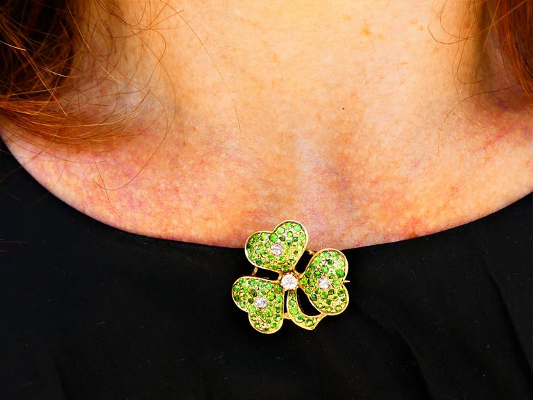 This lovely brooch was crafted around 1900 in 14 karat yellow gold in the shape of a shamrock with three leaves. The rare green demantoid garnets are pavé set and each leave has one round diamond in the center. The largest diamond is located between