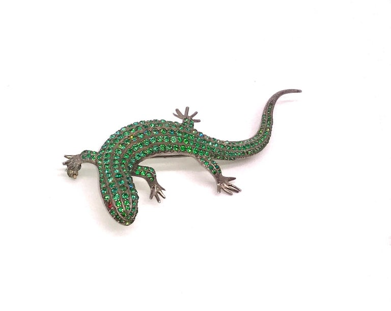 Fabulous emerald lizard form brooch. Set with emerald green pastes on silver, this is a luxurious lizard indeed. The Roman symbol of wedded bliss and popular in jewelry during fin de siecle , our lizard is an example of the realism which prevailed