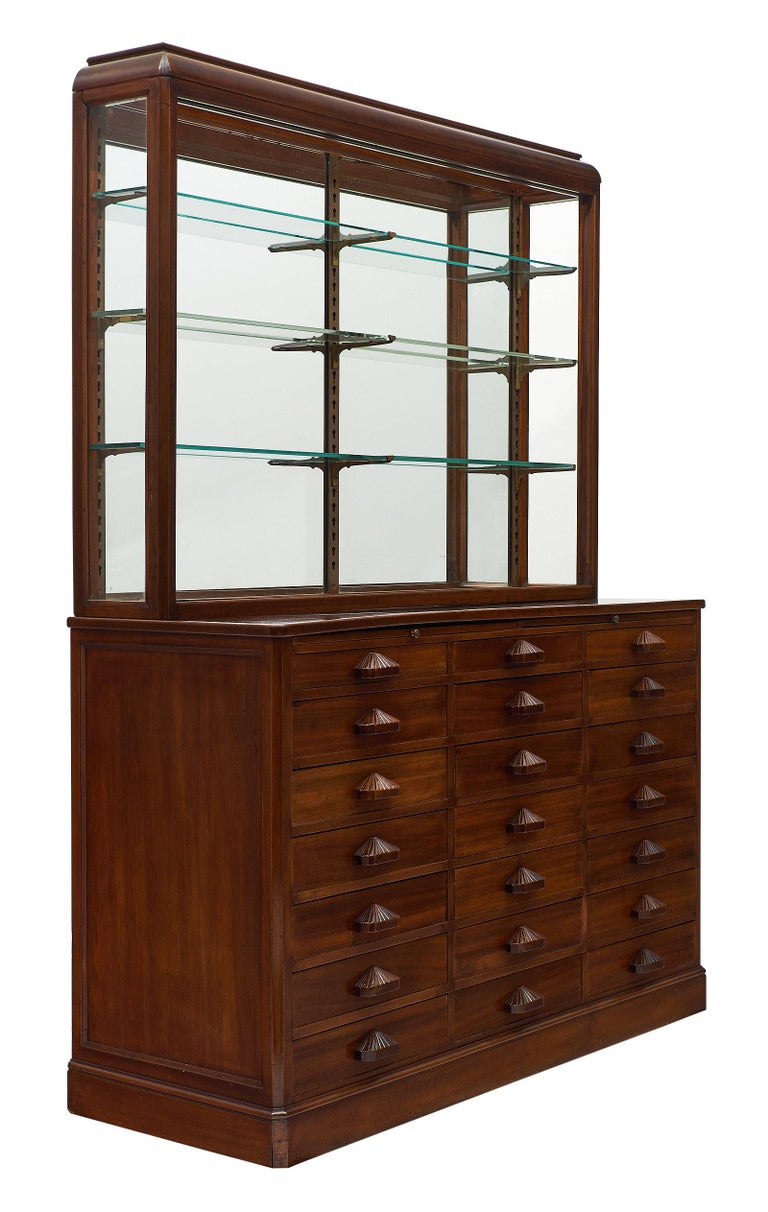 A stunning French Haberdashery cabinet with display case. This piece is made of solid oak with 21 drawers all dovetailed and their original shell shaped handles. There are also two pull-out leaves. An opened vitrine with glass shelves sits on top.