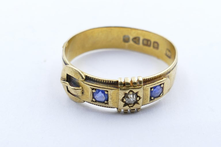 This beautifully preserved Antique (Victorian) Buckle Ring is set with a Diamond as the centrepiece and is flanked by 2 lovely old Ceylon Sapphires, round cut & bead set. The Diamond is old European cut. The Ring features hallmarks pertaining to