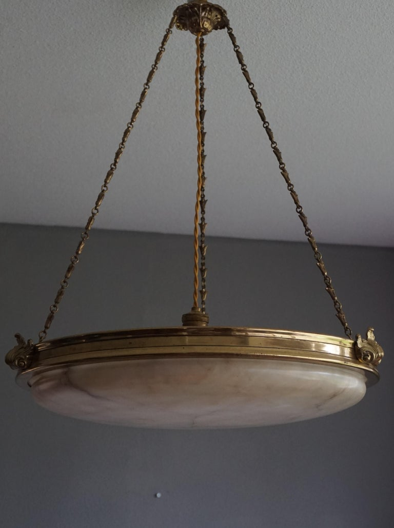 Stunning design alabaster and bronze light fixture.  This stylish and sizeable French antique is an absolute joy to come home to. The unusually flat, but rounded alabaster shade in its magnificent bronze frame gives this unique light fixture its