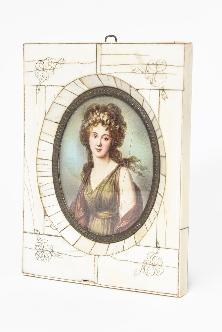 19th century miniature hand-painted portrait of a lady with flowers in her hair presented in an engraved bone rectangular frame with an antique-gilded brass frame.