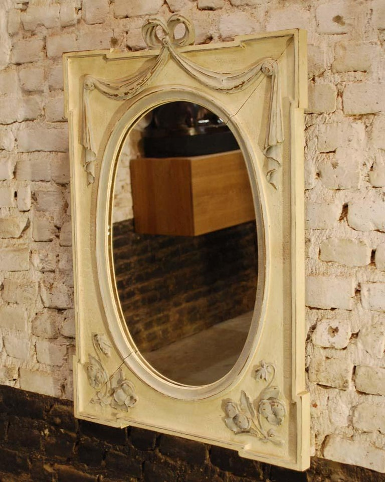 A handsome mirror, hand carved from solid oakwood and painted in natural colors. The mirror has a rectangular shape with an oval mirror. It is adorned with a bow tied ribbon ending in draped curtains. Typical Art Nouveau floral elements were carved