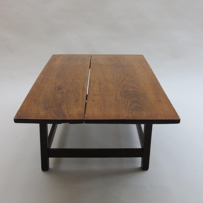 Antique coffee table originally from Japan made from solid hardwood. Dates from the late 19th century. Very nice peg detail to the plank top and wedge jointed base.