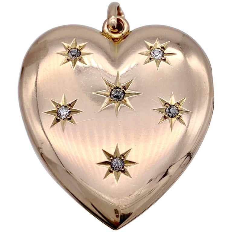 This elegant 14 karat rose gold locket in the shape of a heart is set with six diamonds in star shaped settings. The reverse is beautifully engraved with the initials H and M.