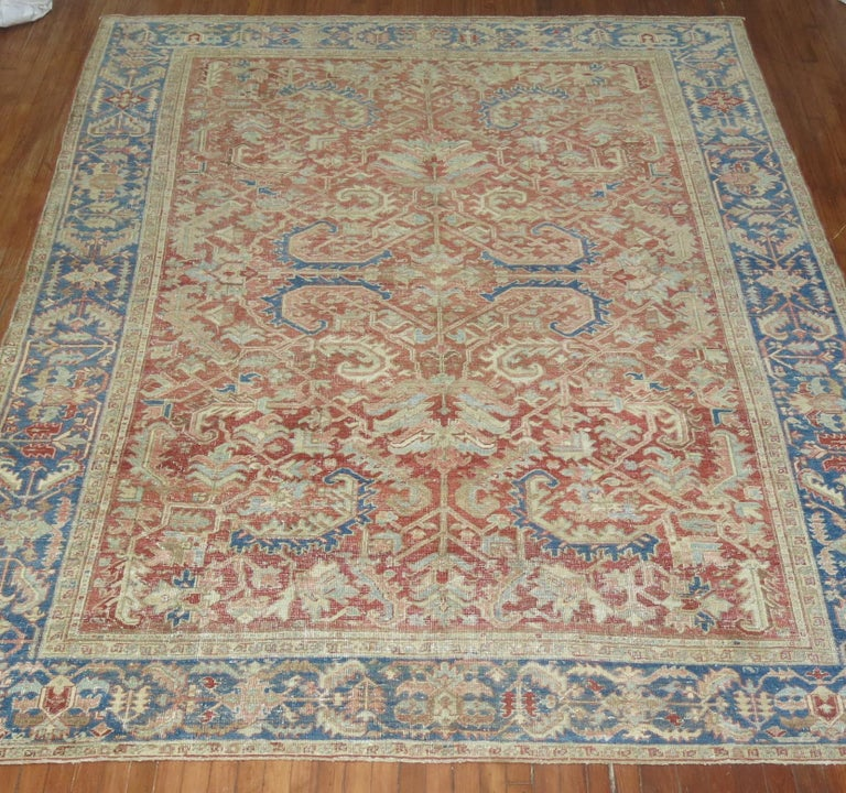 This is an early 20th century handwoven decorative room size Persian Heriz rug . Soft red field with soft blue border. Perfect amount of wear, sturdy enough to handle every-day traffic.  With distinctive large-scale motifs and a wide ranging